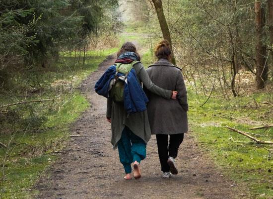 Diana begleitet eine Klientin im Gespräch auf einem Waldspaziergang